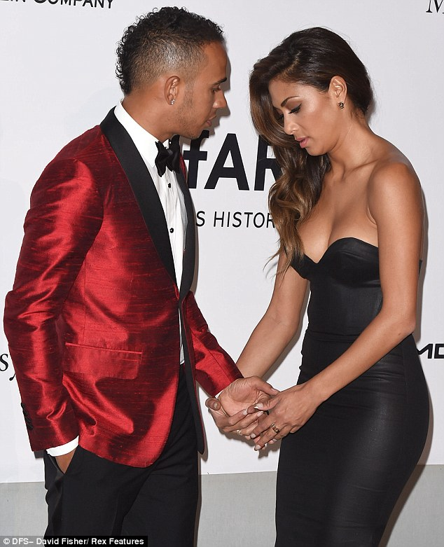 United front: When it came to their red carpet display, Lewis and Nicole were more tactile than ever, cuddling up as they worked their magic, with the singer even tending to her man's suit as she ensured they were preened to perfection