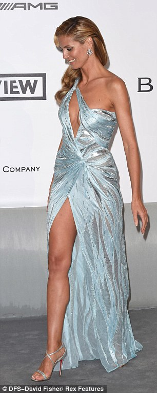 Still got it: The supermodel stunned in a slinky pale blue number accented by silvery threading, and sexy details included a cleavage-exposing cut-out and leg-baring slit in the skirt