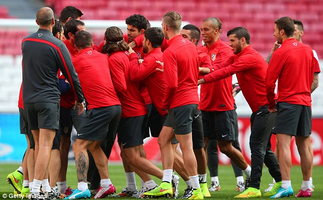 In the mix: Costa (centre) shares a joke with team-mates as spirits were high before training