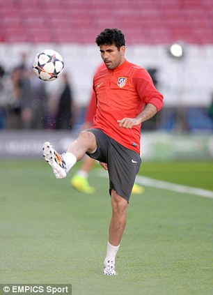 Eye on the ball: Costa kicks a ball around before having a conversation with an Atleti physio
