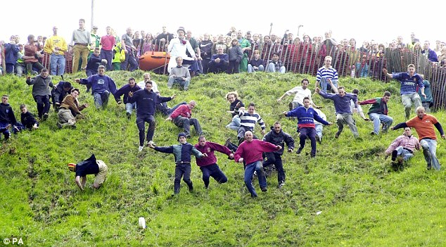 Competitors run after a Double Gloucester cheese down Cooper's Hill, near Brockworth, Gloucestershire, during the famous race in 2006. The event is in the constant shadow of health and safety bans
