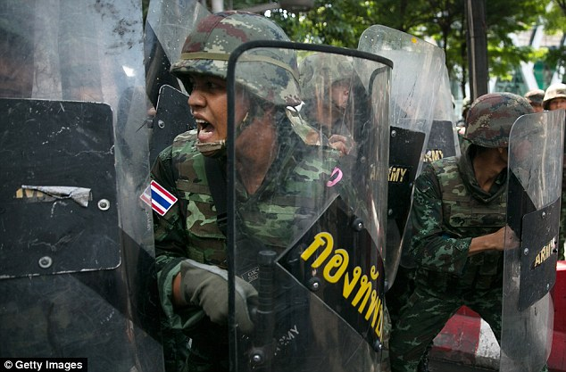 Tension: A Thai soldier shouts from behind a wall of riot shields as protesters threaten them
