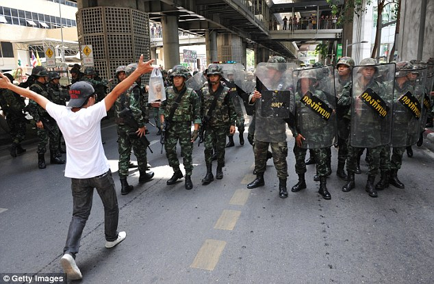 Confrontation: A protester confronts soldiers in riot gear during a city centre anti-coup rallly