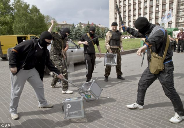 Unrest: Although there were no reports of fighting, these Pro-Russian militants smashed ballot boxes in front of the seized regional administration building in Donetsk