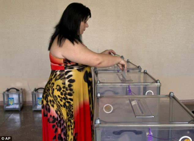 Uneasy: A woman casts her vote for the presidential election in Krasnoarmeisk today