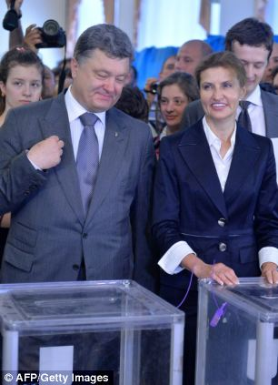 Ukrainian presidential candidate Petro Poroshenko crosses himself as he and his wife Marina cast their votes