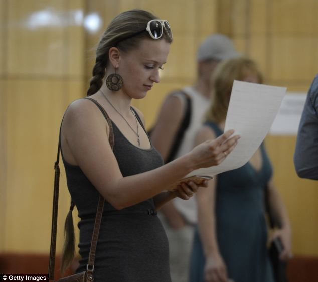 Far from home: A Ukrainian woman resident in Moscow, checks the voter list before choosing her candidate at the Ukrainian Embassy in Moscow