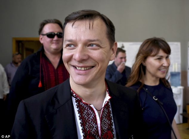 Another candidate Oleh Lyashko smiles while voting at a polling station in Kiev
