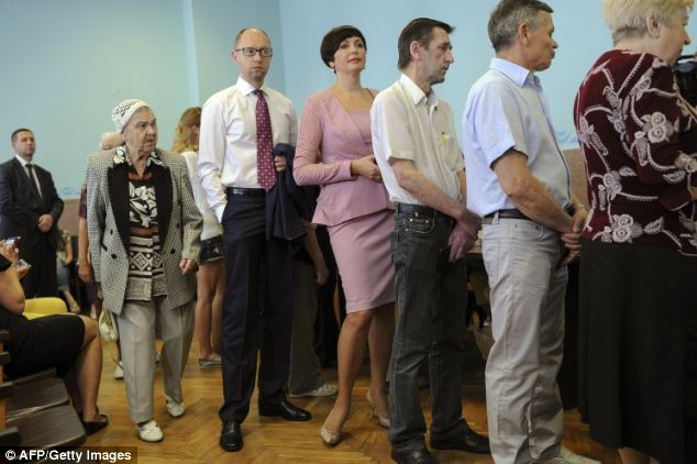 Preparations:  Prime Minister Arseniiy Yatsenyuk and his wife queue in Kiev to get their ballot papers