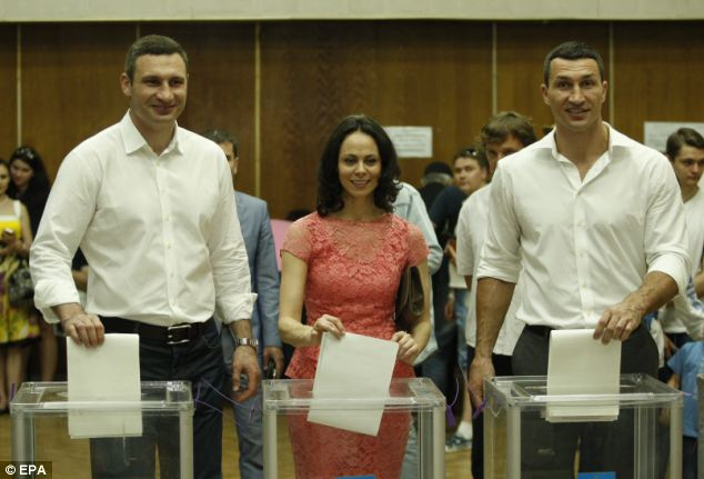 Out for the count: Vitali Klitschko, his wife Natalia Egorova and his brother, fellow heavyweight boxer Wladimir Klitschko add their papers to the ballot boxes