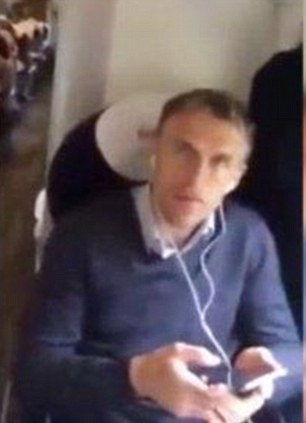Peace and quiet: Phil Neville listens to some music while sitting on the train