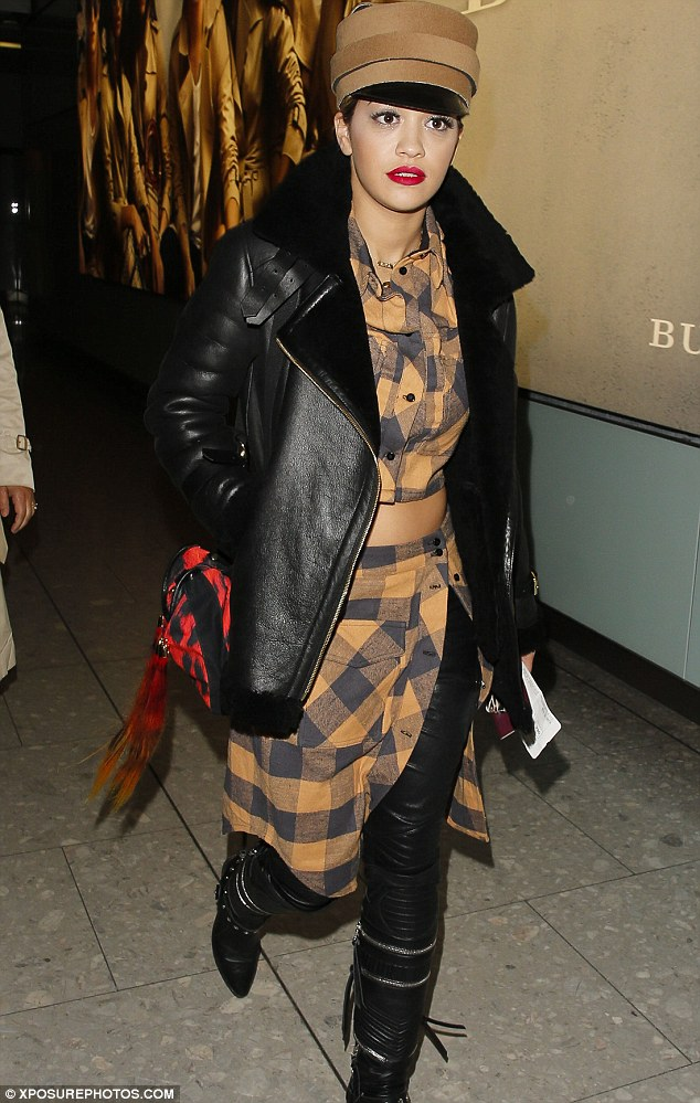 Back in London: Rita also made sure she showed off her toned tum in a matching lumberjack shirt and added a rock chick vibe to her look courtesy of a leather jacket and matching knee-high boots