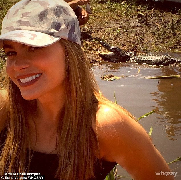 It's gator time! The 41-year-old posed with near swamp occupied by an alligator