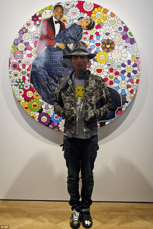 Having fun, fun, fun: Pharrell Williams grinned as he posed next to one of the specially commissioned pieces at an opening party for an art exhibition he co-curated at the Perrotin Gallery in Paris on Monday