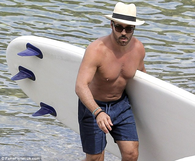 Surfs up: The hunky actor accessorised his beach look with turquoise and brown beaded bracelets