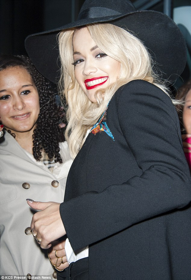 Pearly whites: Rita flashes a big grin as she says hello to fans outside the studio