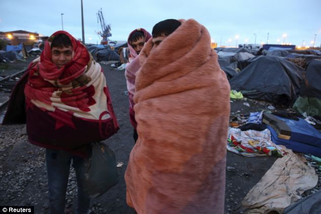 Afghan immigrants use blankets to keep warm near makeshift shelters before French police evacuated them