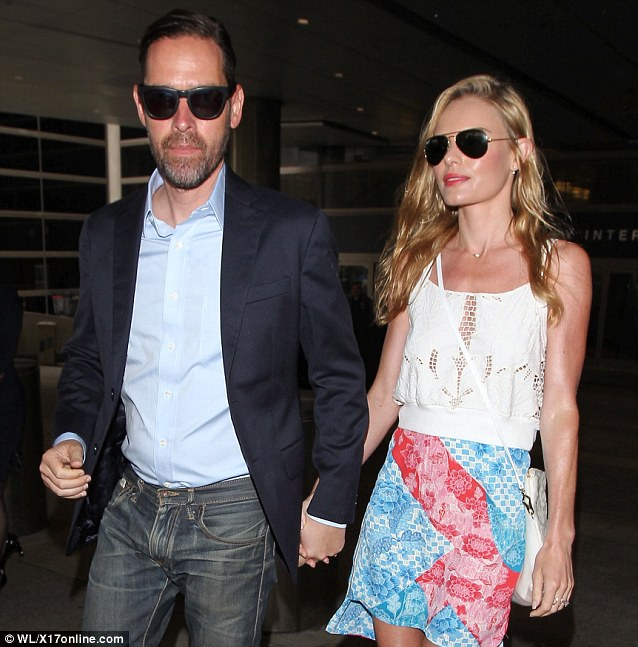 Stylish: The director wore a navy blazer while his wife wore a lacy white tank top and floral miniskirt