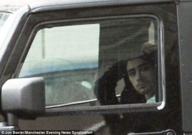First appearance: Zayn Malik looked glum as he was driven away from The Lowry Hotel in Salford yesterday in what is his first appearance since the controversial video emerged