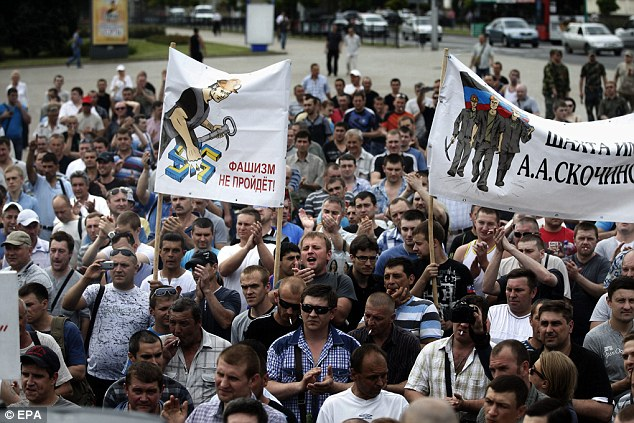 Unrest: Miners take part in a rally against the actions of the Ukrainian military in Donetsk, which killed at least 36 people when retaking the airport from pro-Russian fighters