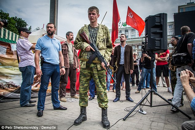 Rising tension: An armed guard of Denis Pushilin protects the PM of the self-proclaimed Donetsk People's Republic in Lenin square, Donetsk