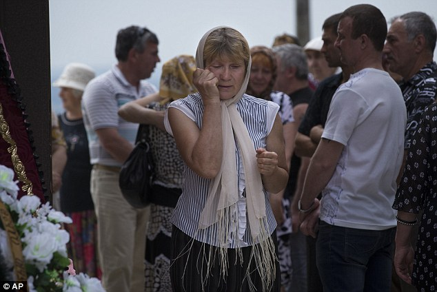 Grief: Mourners attend the funeral for Olga Prokhorenko, 60, and Denis Abramenko, 30, who were killed in the offensive by Ukrainian forces