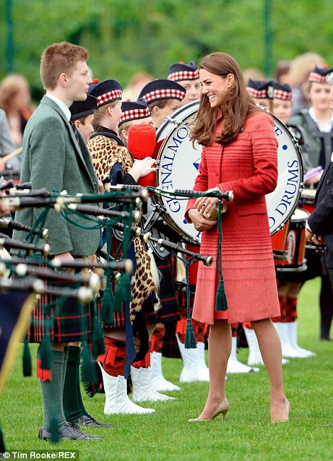 What's your favourite tune? The Duchess of Cambridge beams as she shares a joke with a young piper