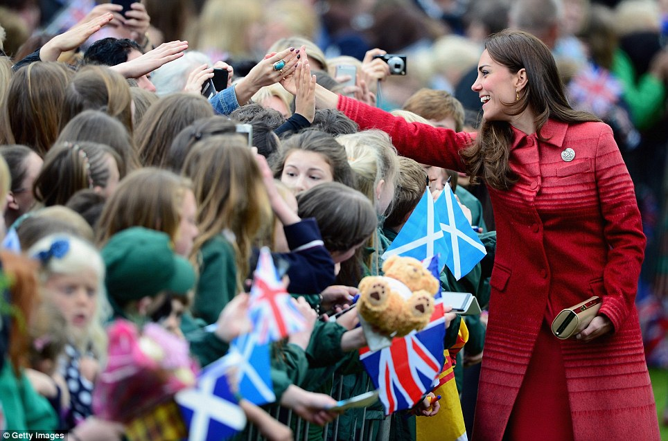 High five! The Duchess of Cambridge beams as she's greeted by a cheering crowd as she arrives at MacRosty Park with the Duke of Cambridge to unveil a plaque
