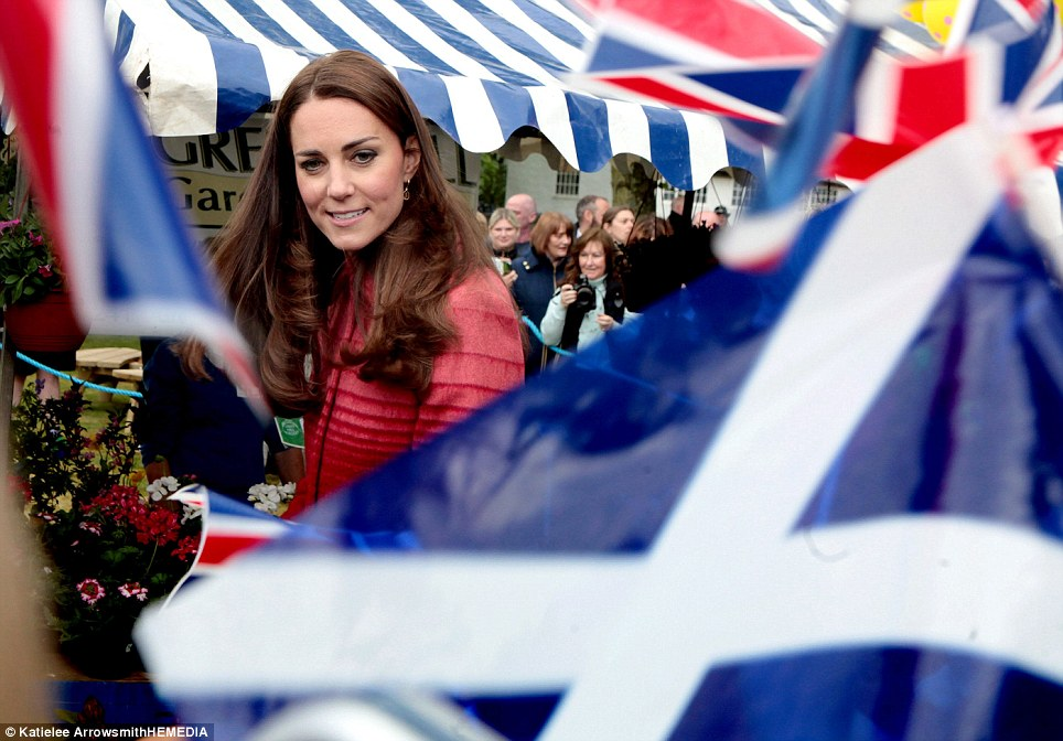 All smiles: The Duchess arrives at Forteviot fete and is almost obscured by a sea of enthusiastically waved Saltire and Union Jack flags