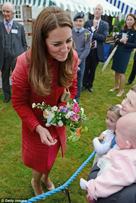 Adorable: The Duchess of Cambridge beams as she's introduced to a baby girl