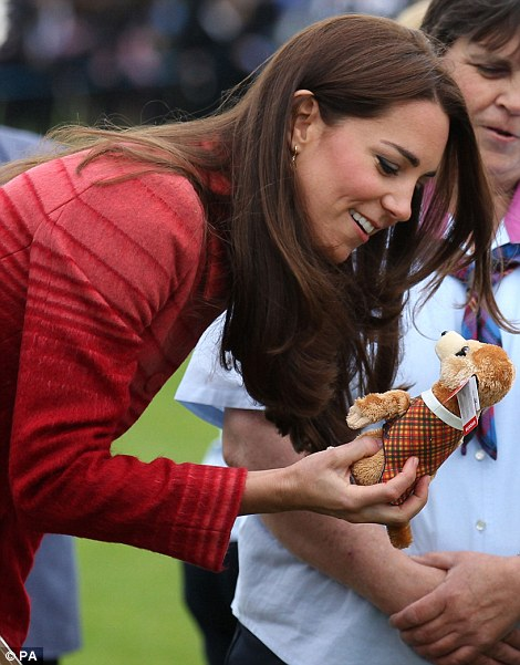Impressed: The Duchess is handed a tiny toy dog for Prince George