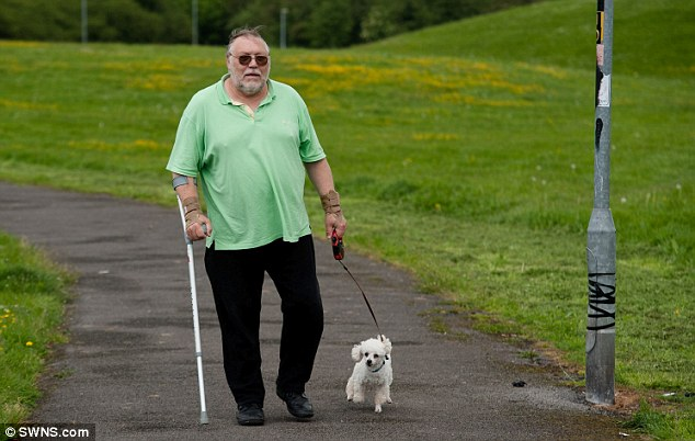 Walkies: Scampie near the offending lamppost in Swindon, with his owner Ernest Reid, 68