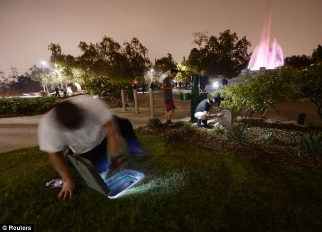 Frantic: People look for hidden cash around the Mulholland Memorial Fountain on Thursday morning after the anonymous millionaire tweeted clues about where he'd hidden cash in Los Angeles