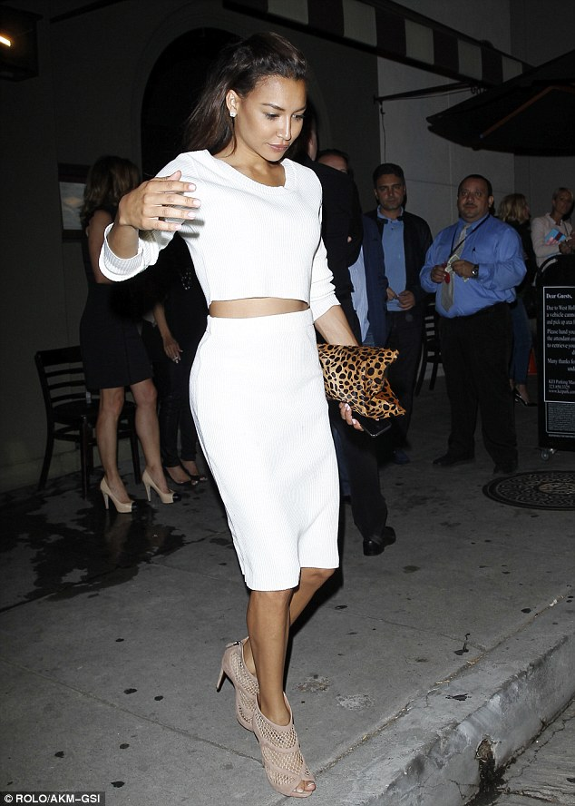 Crop top: The 27-year-old teamed the ensemble with an animal print clutch and a pair of tan peep toe heels