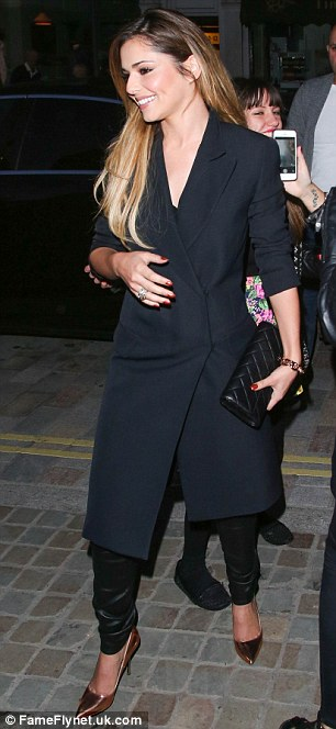 High spirits: Cheryl was in a cheerful mood after arriving at the hugely popular London venue by car