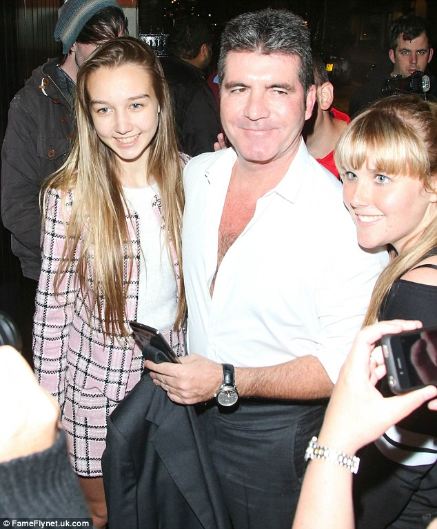 Say cheese: Cowell cheerfully obliges fans with photographs before making his way inside