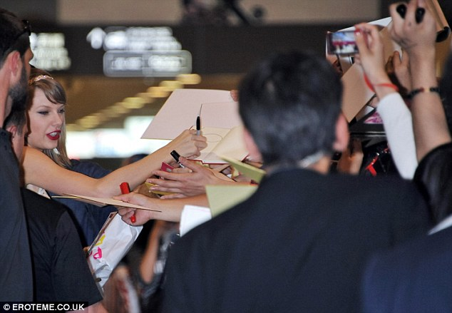 There you go: She signs autographs as fans clamour for her attention