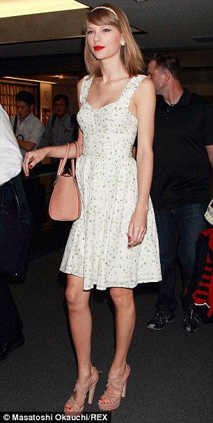 Looking good: Taylor, 24, matched her floral pattern dress with strappy wedge heels and a tan coloured handbag for her arrival in Japan
