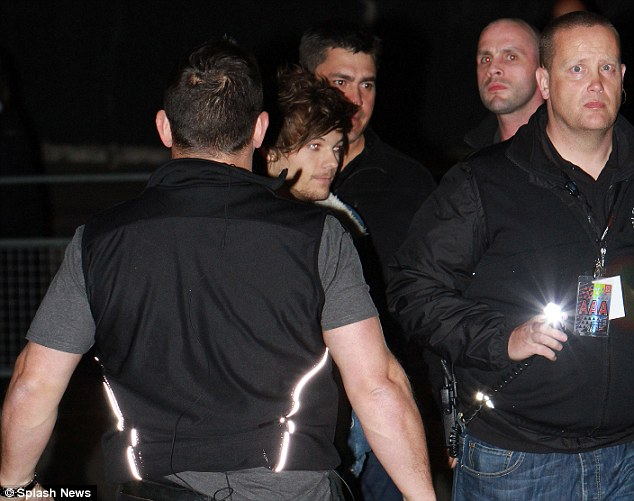 Mobbed: Louis was flanked by members of his security team as she headed to the Manchester city centre venue