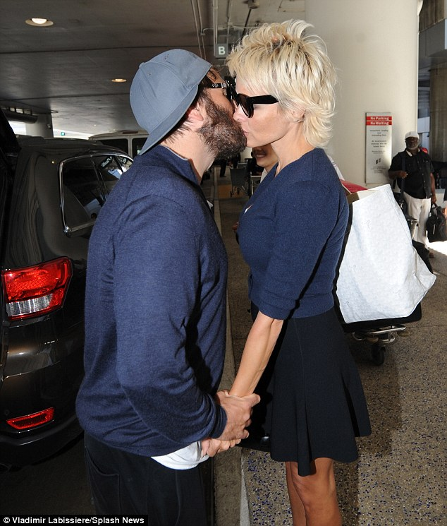 Time for a kiss: Pamela returned to LA with her very attentive husband Rick Salomon who gave a kiss