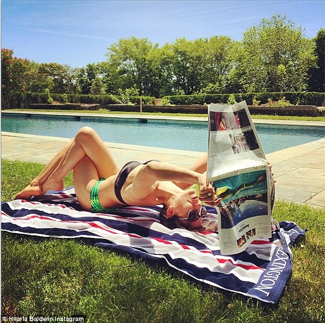 Well-read: Hilaria Baldwin shared a snap on Instagram on Sunday of her performing a yoga move while reading the New York Times - the pages of which contained a feature article written about her