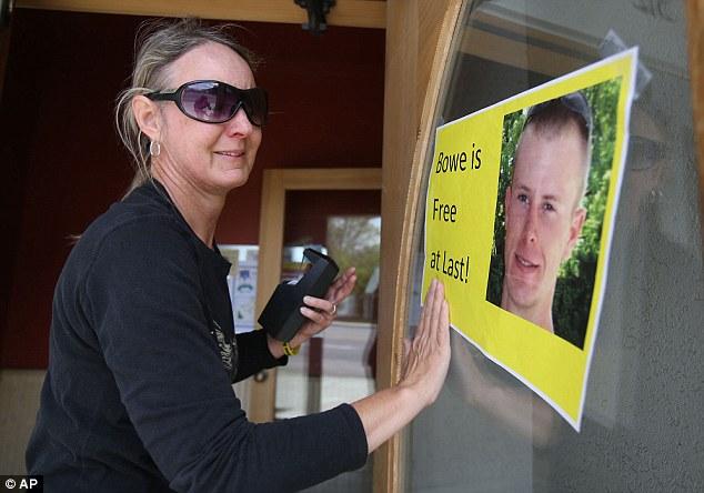 Sondra Van Ert, co-owner of Baldy Sports, hangs a sign celebrating news of Bergdahl's release
