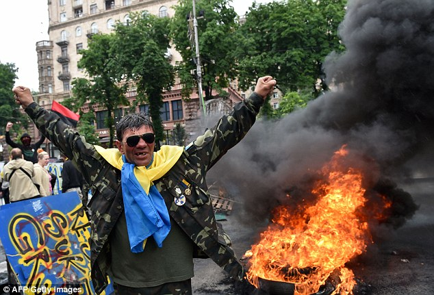 One man raises his arms as fire rages behind him in dramatic scenes in Kiev on Saturday
