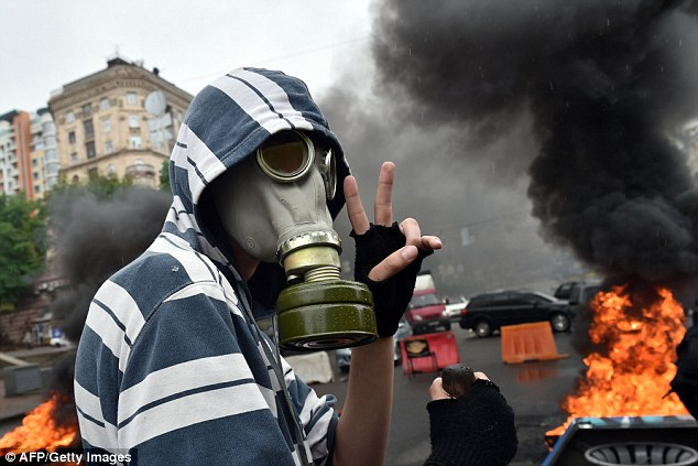 A man wears a gas mask while posing for the camera in front of a raging fire - started to protect the barricade