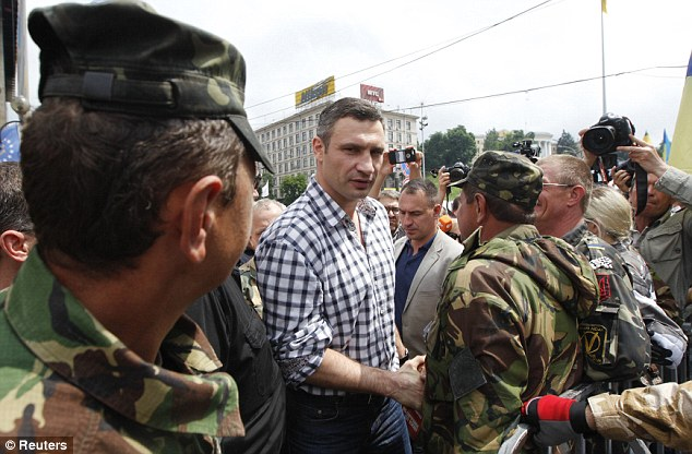 The UDAR (Ukrainian Democratic Alliance for Reform) party leader shakes hands with a member of self-defence units of the Maidan movement