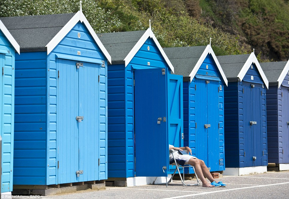 Beach huts: People made the most of the 18C heat yesterday afternoon in Bournemouth, Dorset, after an overcast week