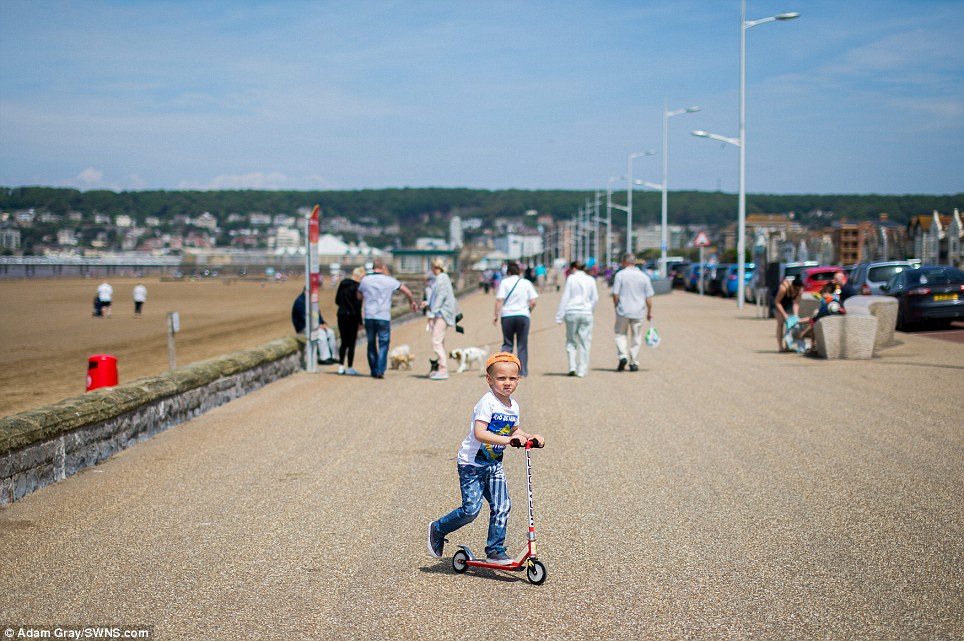 Two wheels: Brodie Souter, five, scooters along the promenade as people make the most of the hot weather in Weston-super-Mare