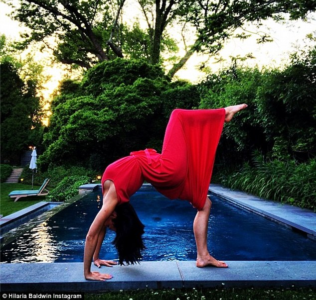Another day, another yoga pose: Hilaria Baldwin performed in a red maxi dress with a peek of sideboob showing on Monday