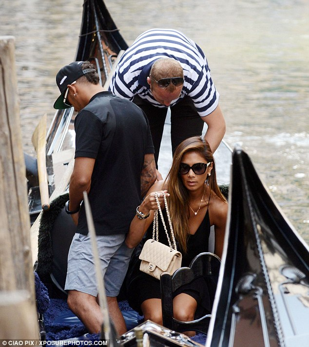 Don't get that wet: Scherzinger took great care to protect her cream Chanel bag