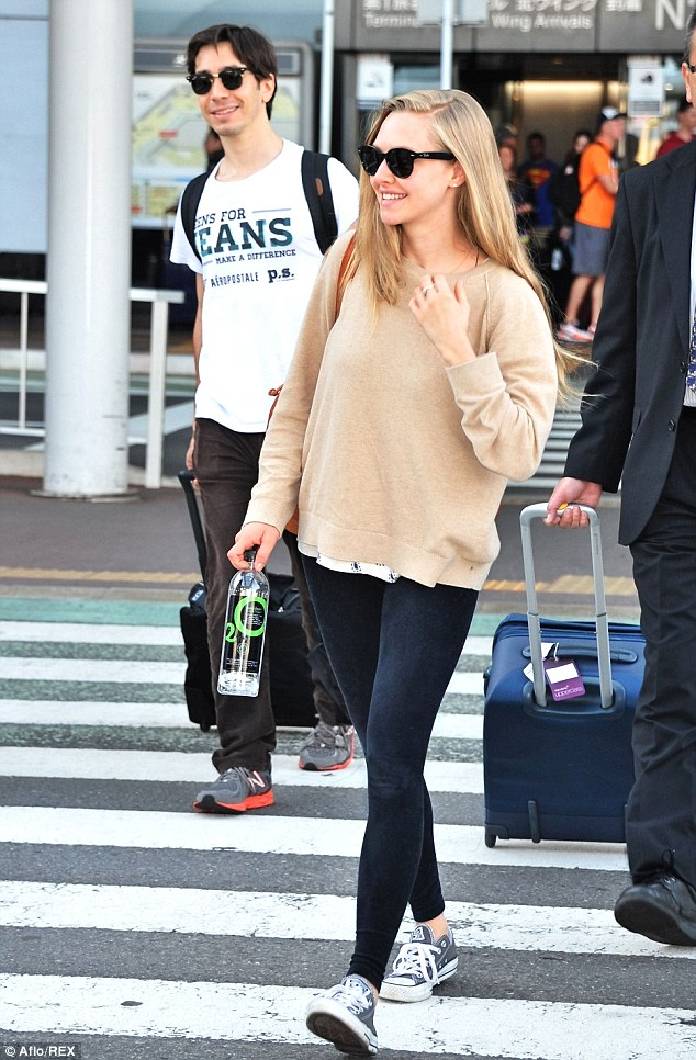 World travelers: Amanda and her birthday boy beau Justin Long arrived n Tokyo to promote Amanda's new movie
